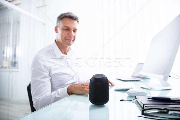 Férfi hallgat drótnélküli hangszóró iroda mosolyog Stock fotó © AndreyPopov