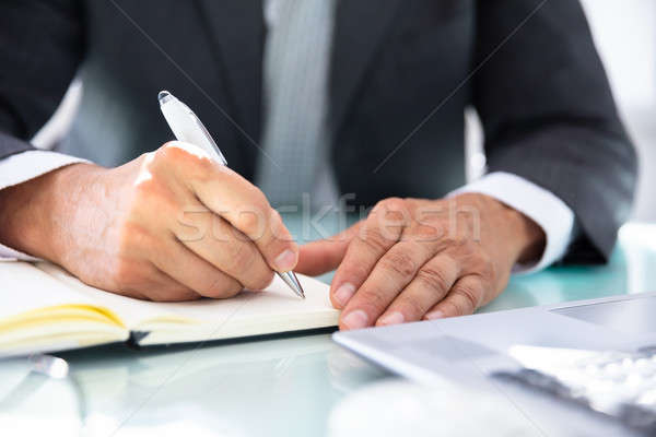 Businessman Writing Schedule In Diary Stock photo © AndreyPopov