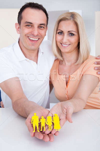 Portrait of happy couple holding family figure cut-out Stock photo © AndreyPopov