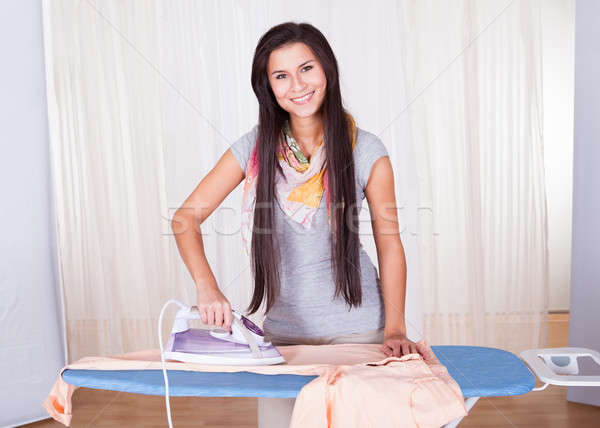 Cheerful housewife ironing the clothes Stock photo © AndreyPopov