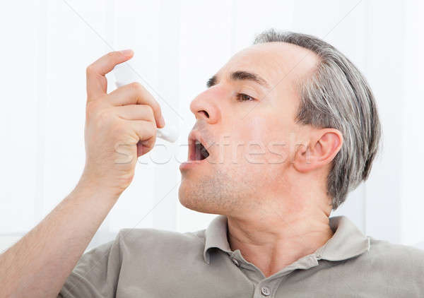 Man with asthma inhaler Stock photo © AndreyPopov