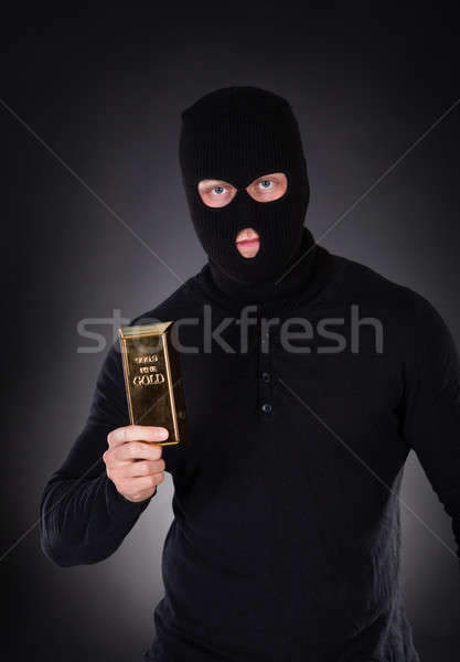Robber holding a gold bullion bar Stock photo © AndreyPopov