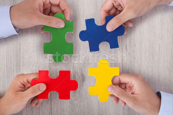 Businesspeople Joining Multicolored Puzzle Pieces At Desk Stock photo © AndreyPopov