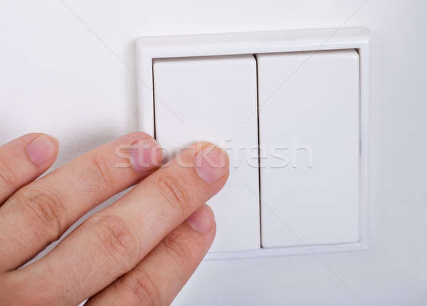 Hand Presses The Light Switch On The Wall Stock photo © AndreyPopov