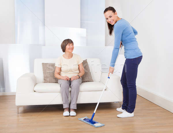 Caretaker Cleaning Floor While Woman Sitting On Sofa Stock photo © AndreyPopov