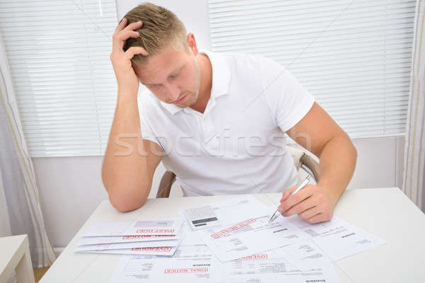 Worried Man Looking At Bills Stock photo © AndreyPopov
