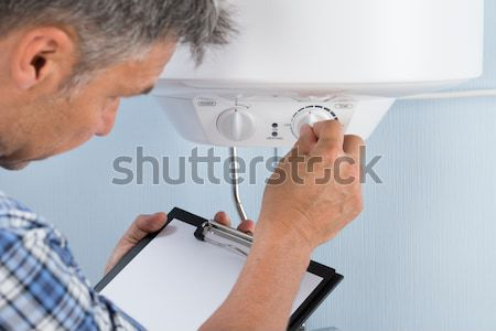 Stock photo: Plumber Adjusting Temperature Of Electric Boiler