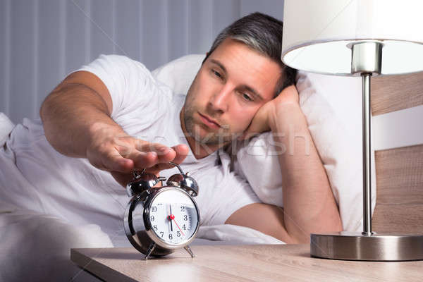 Man Snoozing Alarm Clock Stock photo © AndreyPopov