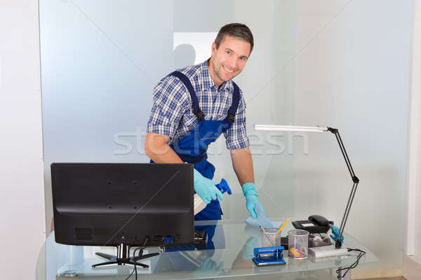 Male Janitor Cleaning Desk Stock photo © AndreyPopov