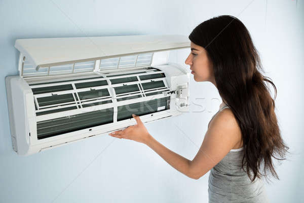 Woman Checking Air Conditioner Stock photo © AndreyPopov