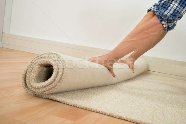 Worker Folding Carpet On Floor Stock photo © AndreyPopov