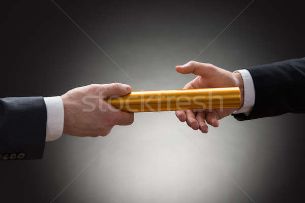 Stock photo: Two Hands Passing A Golden Relay Baton