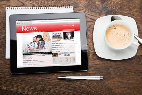 Tea Cup And Digital Tablet With Business News Stock photo © AndreyPopov