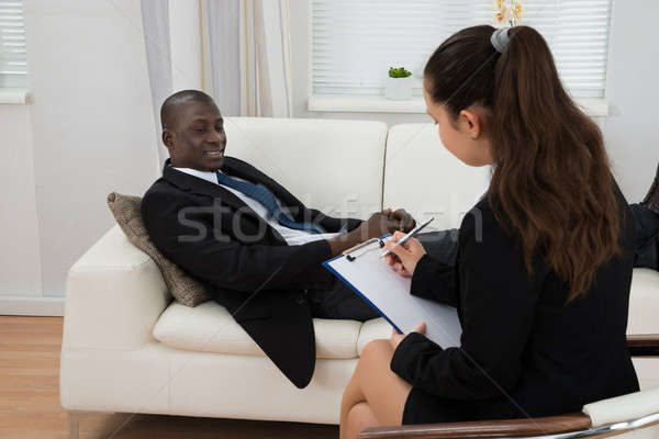 Patient In Front Of Psychiatrist Taking Notes Stock photo © AndreyPopov