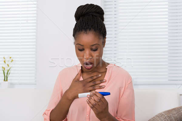 Stock photo: Shocked Woman With Pregnancy Test Kit
