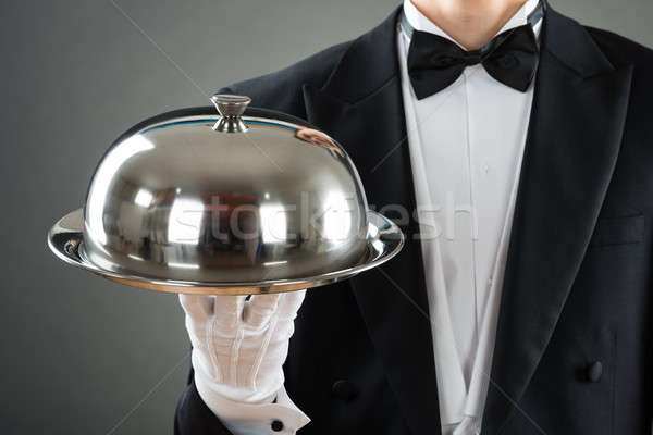 Midsection Of Waiter Holding Tray With Cloche Stock photo © AndreyPopov