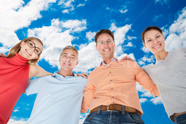 Happy Friends Forming Huddle Against Sky Stock photo © AndreyPopov