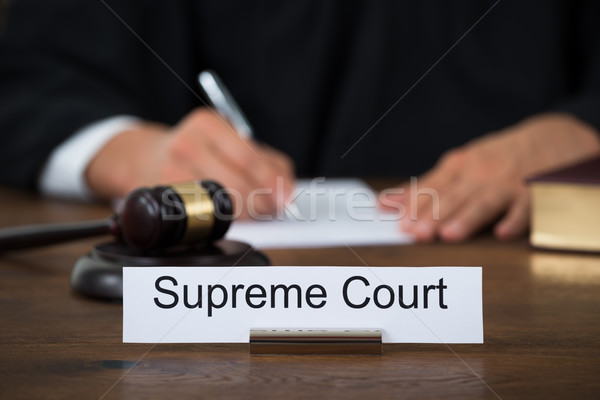 Supreme Court Nameplate With Judge Writing On Paper Stock photo © AndreyPopov