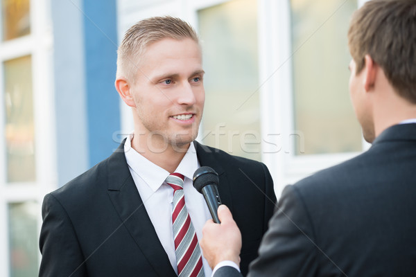 Journalist Taking Interview Of Smiling Businessman Stock photo © AndreyPopov