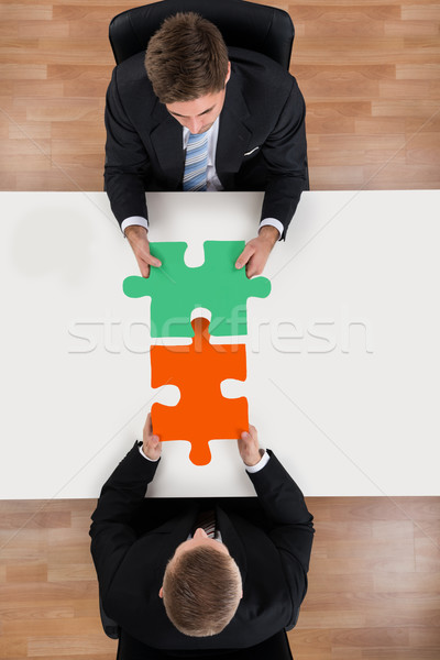 Businessmen Assembling Jigsaw Puzzle At Desk Stock photo © AndreyPopov