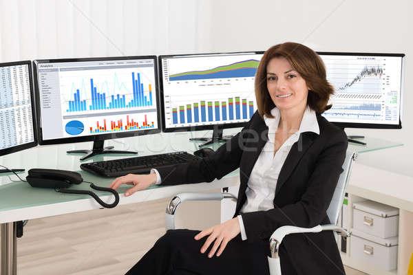 Femme d'affaires graphiques multiple ordinateurs heureux jeunes Photo stock © AndreyPopov