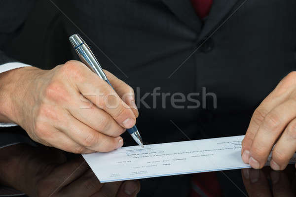 Close Up Of Businessman Filling Blank Cheque At Desk Stock photo © AndreyPopov