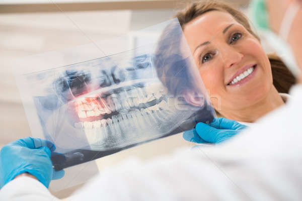 Dentist With Teeth X-ray In Front Of Woman Stock photo © AndreyPopov