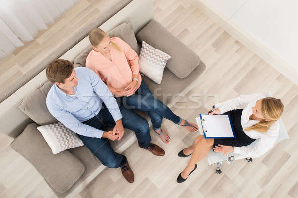 Couple Sitting On Sofa With Psychologist At Home Stock photo © AndreyPopov