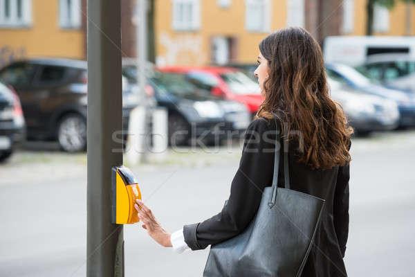 Businesswoman Pressing Yellow Crosswalk Button Stock photo © AndreyPopov