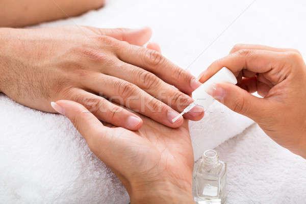 Manicurist Applying Moisturizing Oil On Person's Hand Stock photo © AndreyPopov
