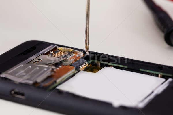 Gebroken mobiele telefoon schroevendraaier telefoon man Stockfoto © AndreyPopov