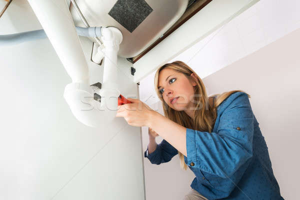 Close-up Of Woman Fixing Sink Pipe With Wrench Stock photo © AndreyPopov