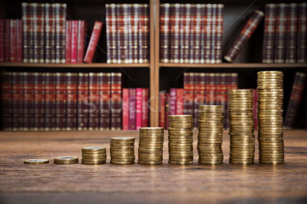 Stock photo: Stacked Coins On Wooden Desk In Courtroom