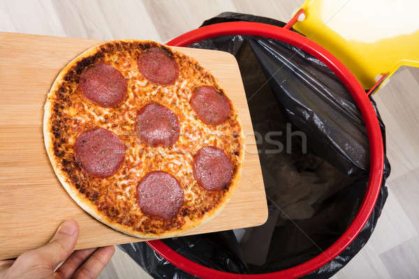 Person Throwing Salami Pizza In Dustbin Stock photo © AndreyPopov