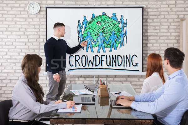 Businessman Showing Crowd Funding Concept In Office Stock photo © AndreyPopov