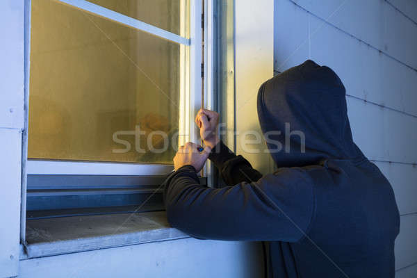 Stock photo: Robber Using The Crowbar To Open The Glass Window