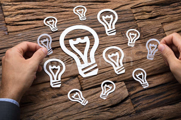 Businessman Arranging Paper Light Bulbs Stock photo © AndreyPopov