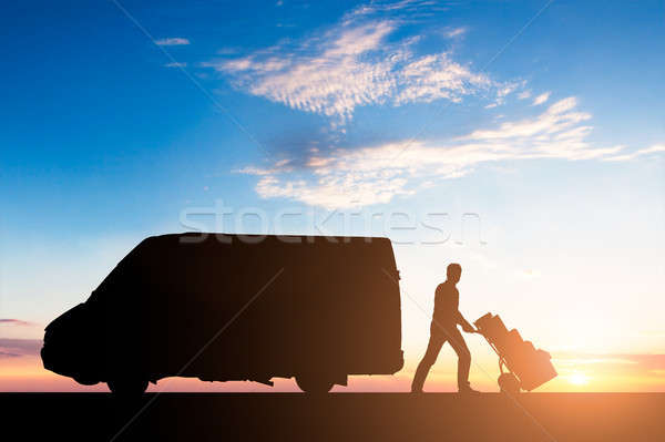 Silhouette Of Delivery Courier With Cardboard Boxes On Trolley Stock photo © AndreyPopov