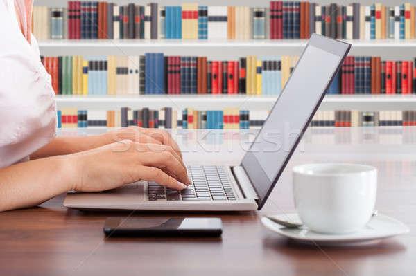Zdjęcia stock: Kobieta · za · pomocą · laptopa · biblioteki · kubek · stolik