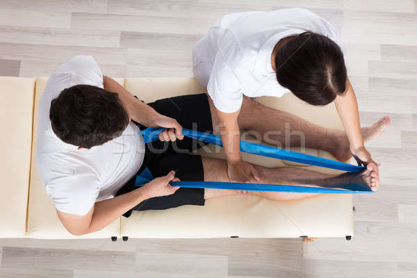 Female Therapist Assisting Patient While Exercising Stock photo © AndreyPopov