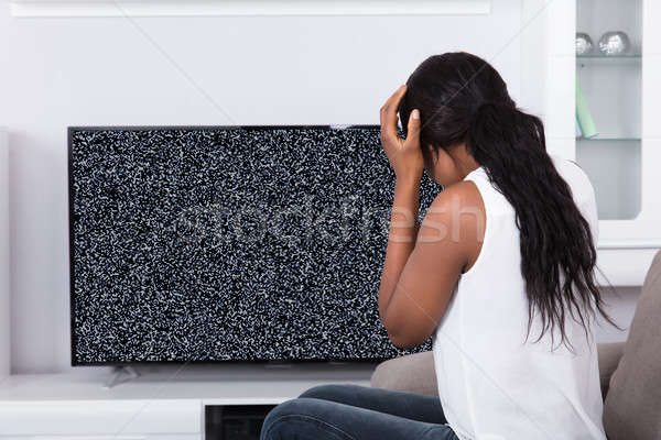 Woman Sitting On Sofa Near Television With No Signal Stock photo © AndreyPopov