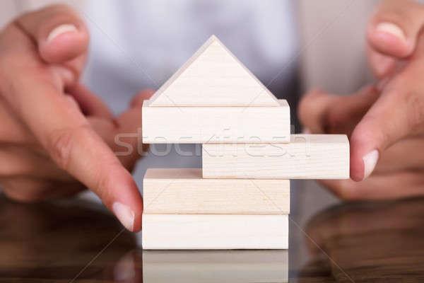 Businesswoman Removing Wooden Block From Model House Stock photo © AndreyPopov