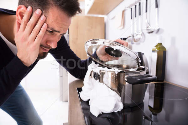 Stock photo: Man Looking At Spilling Out Boiled Milk From Utensil