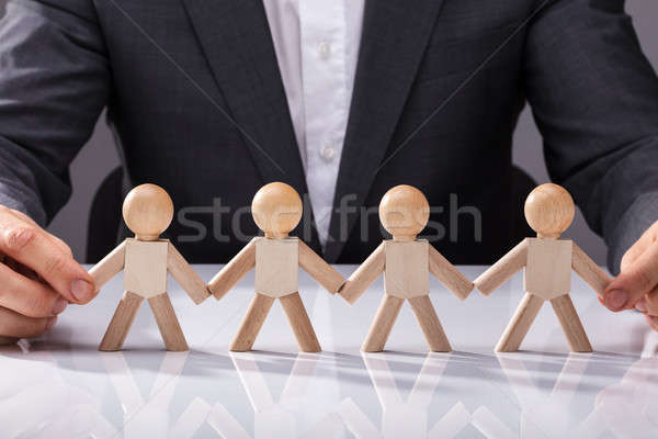Person Holding Hand Of Wooden Figures Stock photo © AndreyPopov