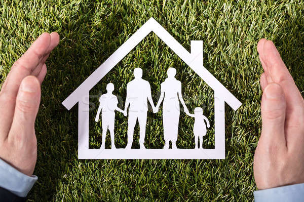 Person Holding Family Home On Grass Stock photo © AndreyPopov