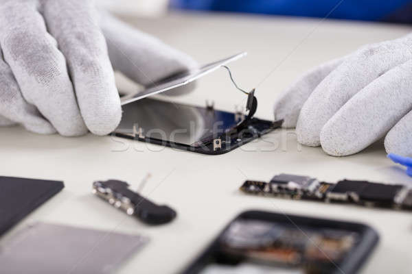 Stock photo: Person Fixing Damaged Screen Of Mobile Phone