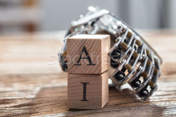 Robot's Hand Holding Wooden Blocks With A And I Alphabet Stock photo © AndreyPopov