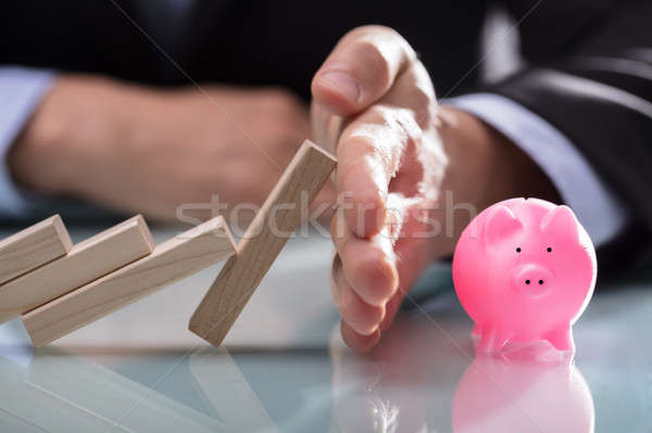 Businessman Stopping Wooden Blocks From Falling On Piggybank Stock photo © AndreyPopov