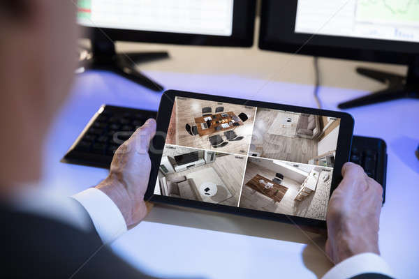 Businessman Looking At CCTV Camera Footage On Digital Tablet Stock photo © AndreyPopov