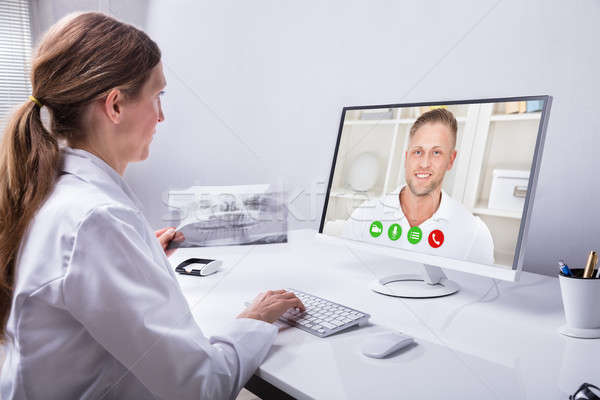 Dentist Video Conferencing With Man On Computer Stock photo © AndreyPopov